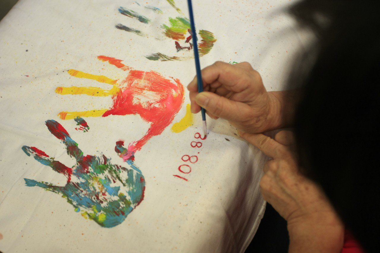 一家人輪流將自己塗滿五顏六色的手掌印在T shirt上,最後還特地標註了日期。圖...