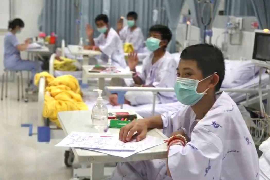 脫困的少年7月11日在清萊醫院隔離病房戴著面罩向外界打招呼。(法新社)