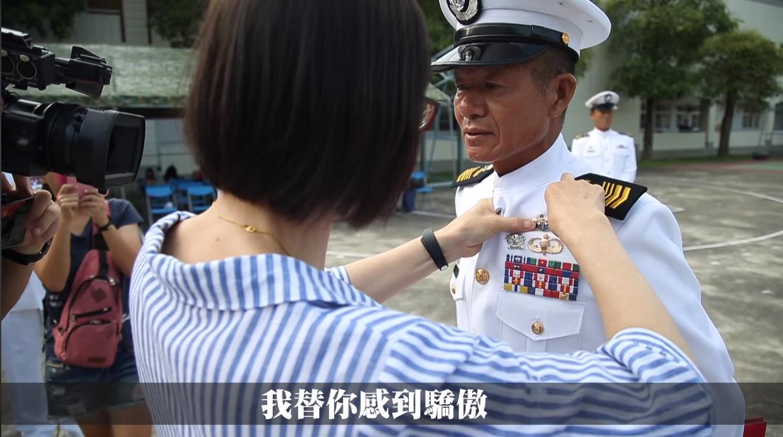 何朝明的太太為他繫上徽章,恭喜他完成水中爆破專長班的挑戰。圖擷自國防部發言人