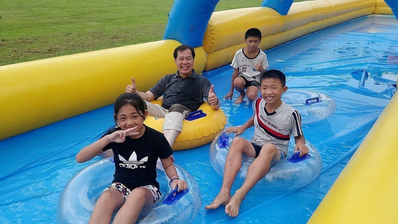 嘉義縣副縣長吳芳銘,和學童一起體驗高台滑水道。 記者卜敏正/攝影