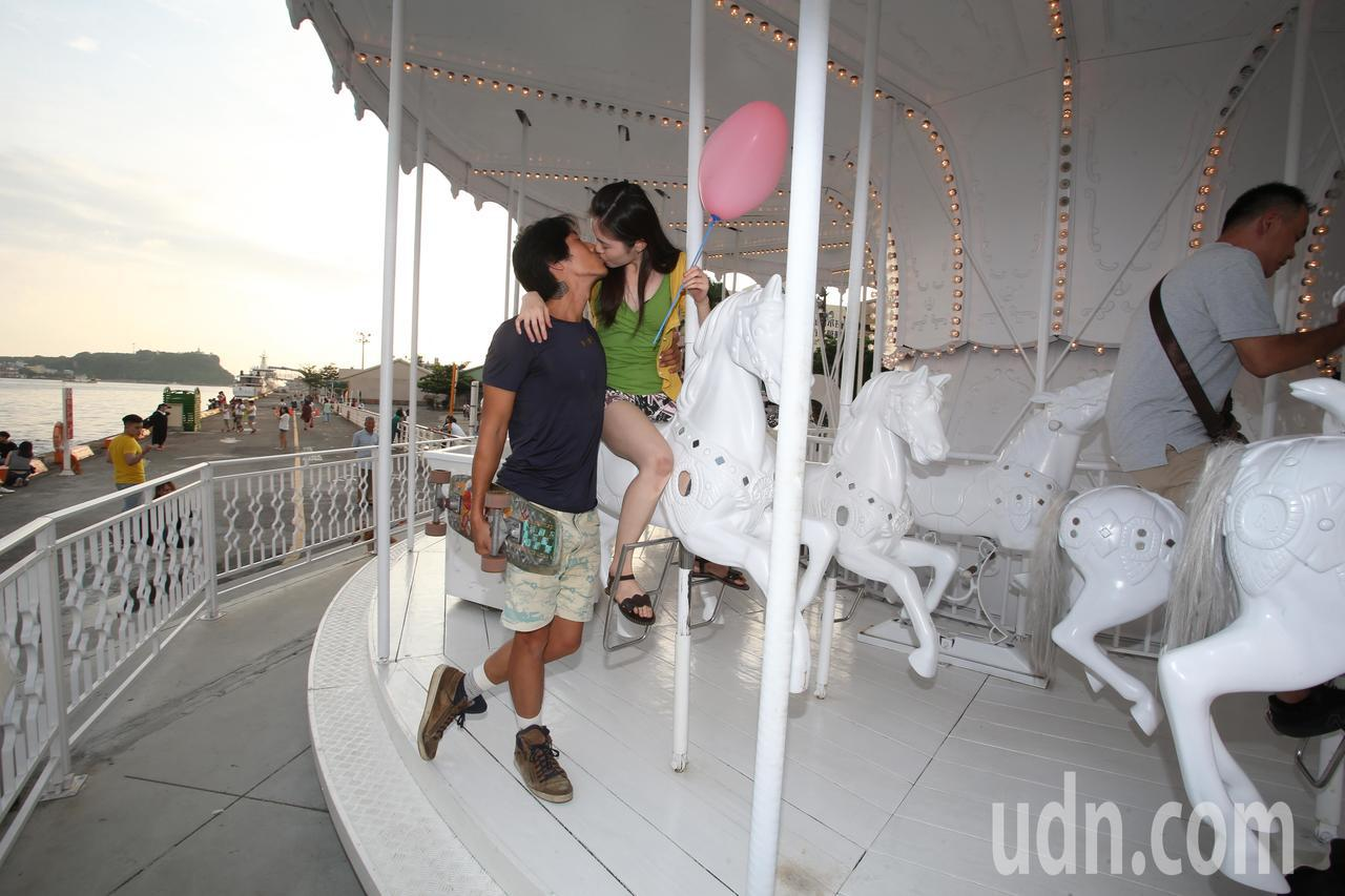 迎接七夕情人節到來,一對年輕情侶搭乘最夯的白色旋轉馬車,忍不住浪漫親吻。高雄市觀...