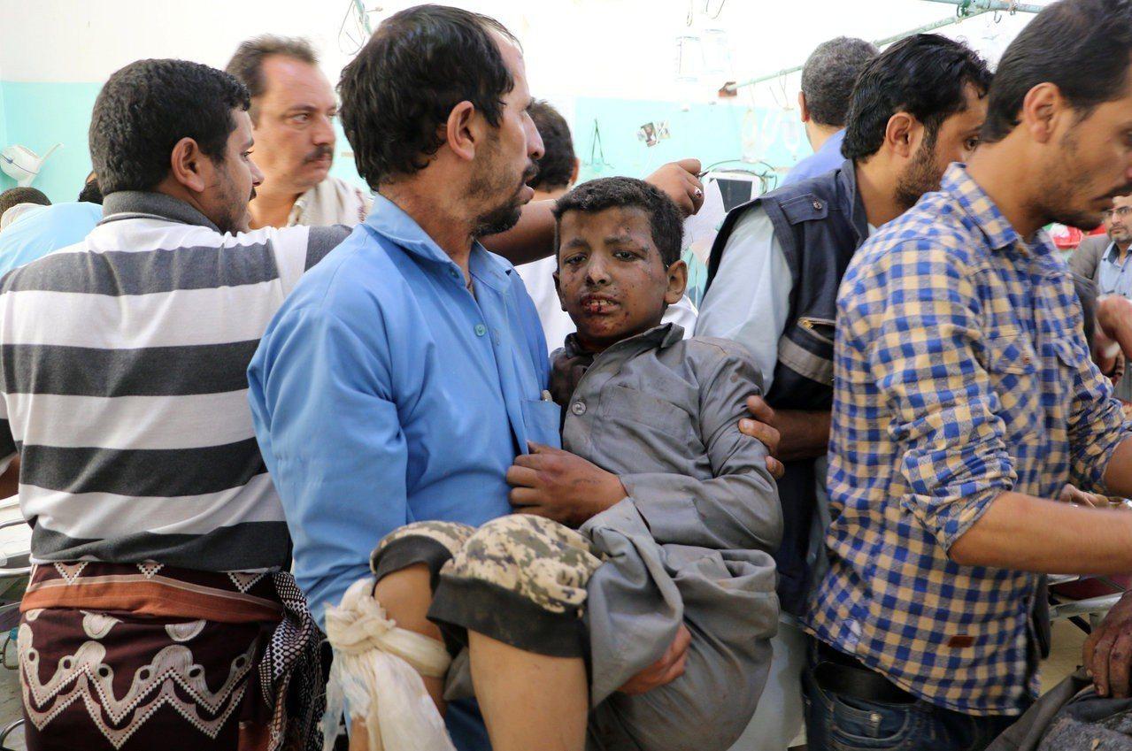 1名葉門男子抱著受傷男童等待治療。路透