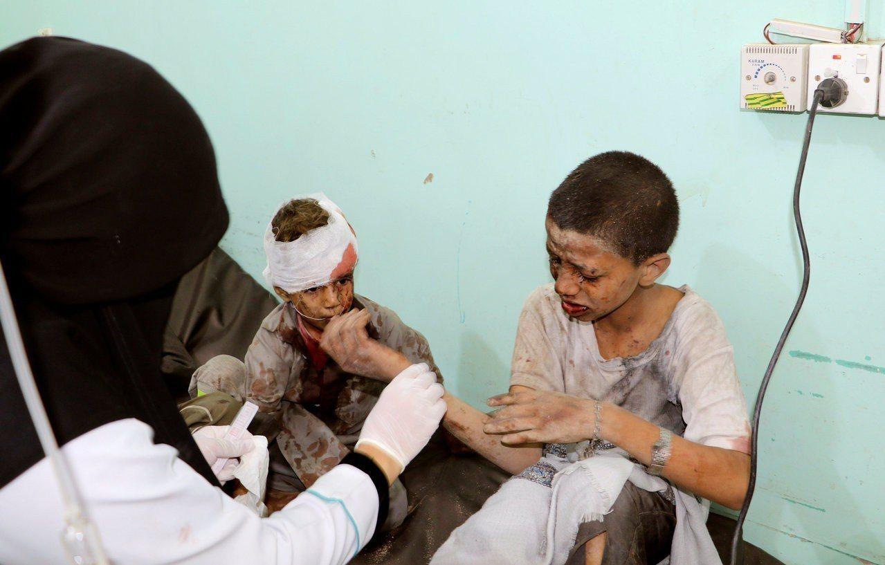 兩名受傷兒童正接受一名醫生治療。路透