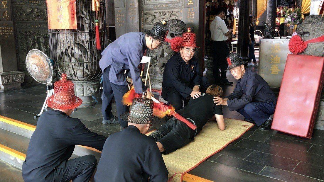 男生「大改」要脫鞋趴在竹蓆上,由班頭壓著持杖「打屁股」。記者蔣繼平/攝影