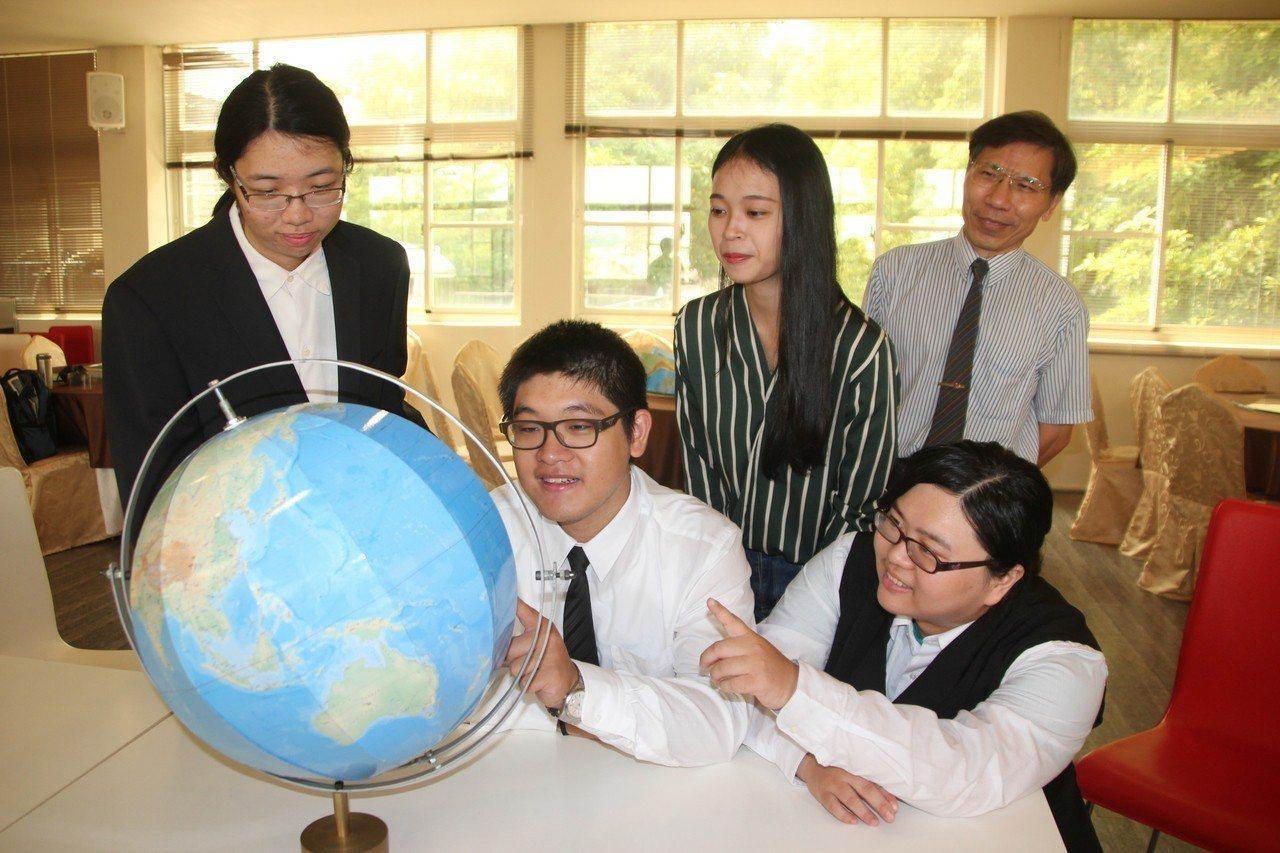 建國科技大學觀光系助理教授林志重(右後)指導學生利用地理資訊系統(GIS)印出地...