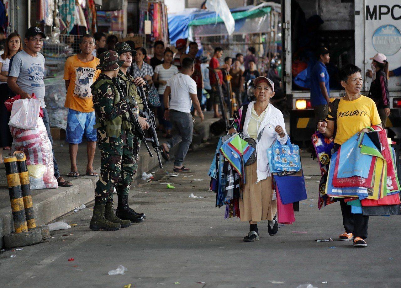 7月31日菲律賓南部發生汽車炸彈攻擊,造成11人喪生,圖為攻擊後軍方在街上站崗。...
