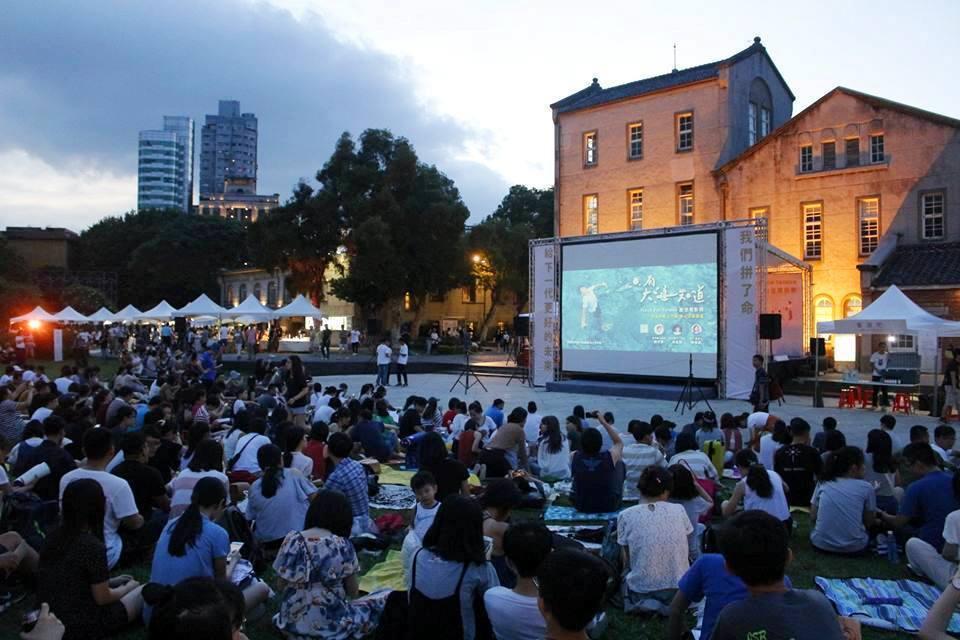 入夜後,更多的人來「夏日嘉年華」的現場,並肩坐著,等著待會兒要播出的電影《只有大...