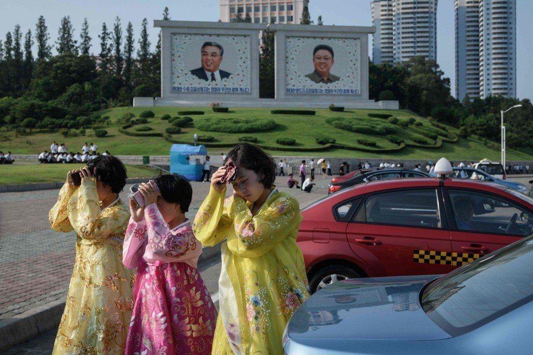 平壤高溫炎熱,穿傳統韓服的女性用身邊小物遮擋烈陽。 (法新社)