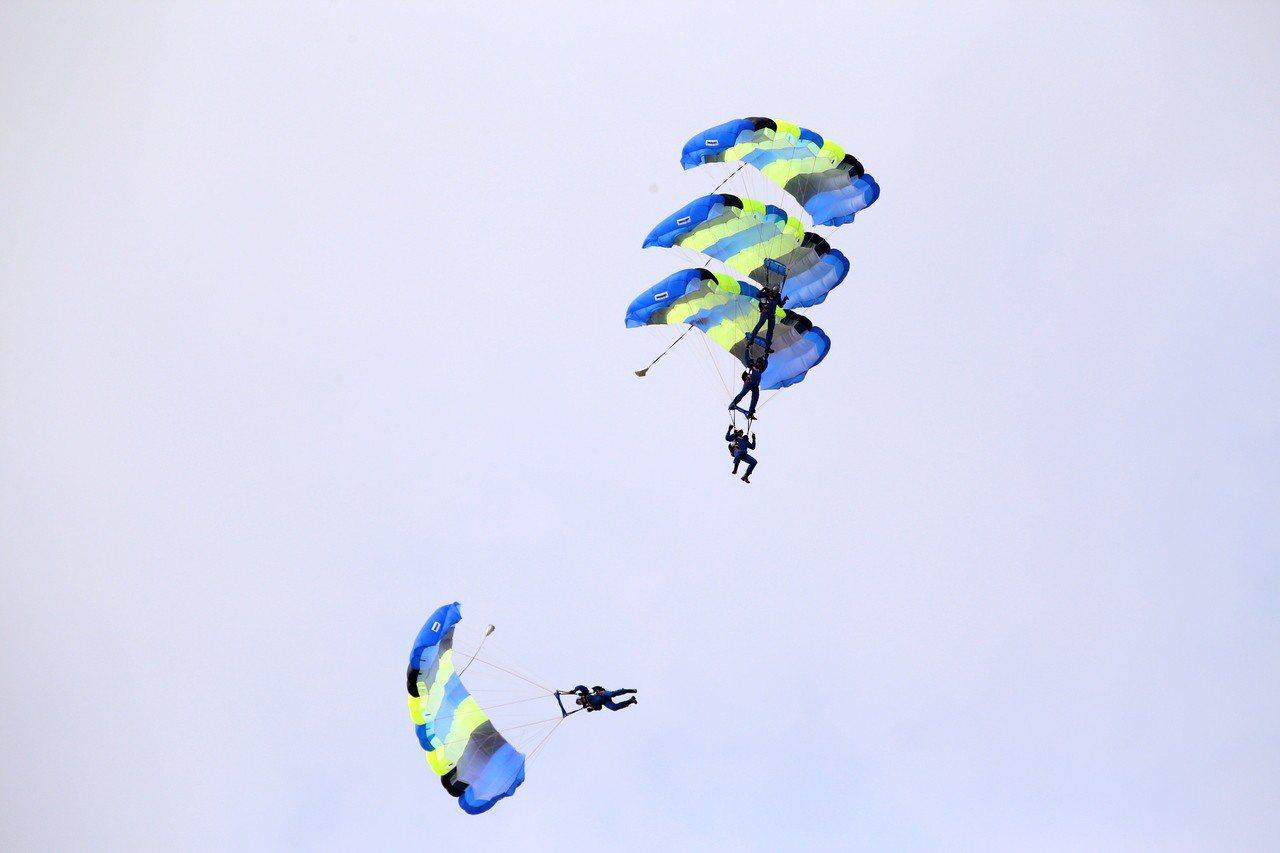 空軍嘉義基地明天開放,日前預演,神龍小組從高空中一躍而下定點著陸,4人疊傘特技空...