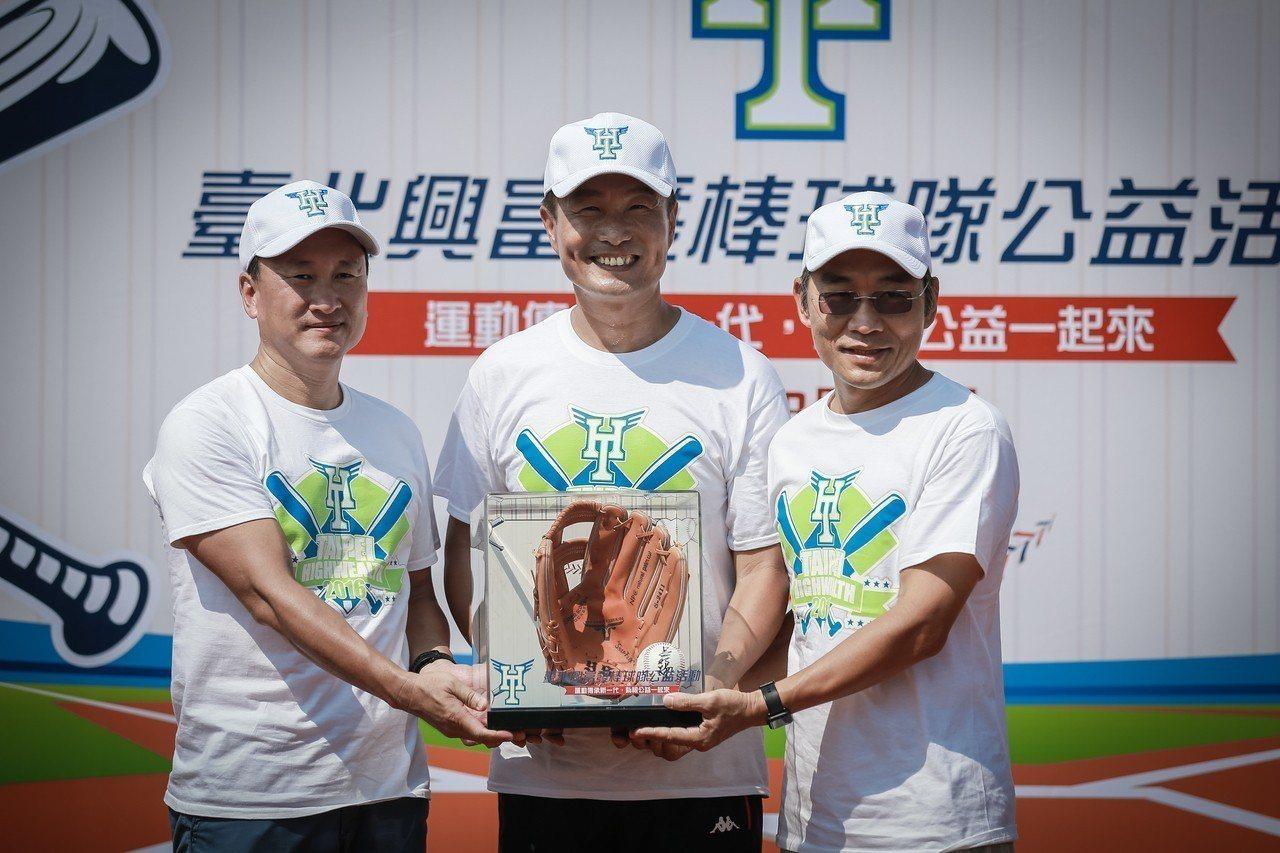 興富發建設董事長鄭志隆(左起)與臺北市政府體育局局長李再立一同致贈棒球與棒球手套...