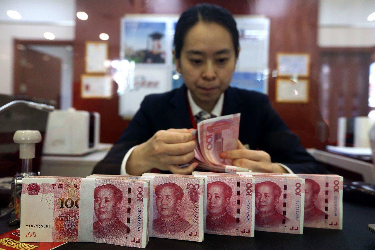 圖為銀行工作人員正在清點鈔票。中新社資料照