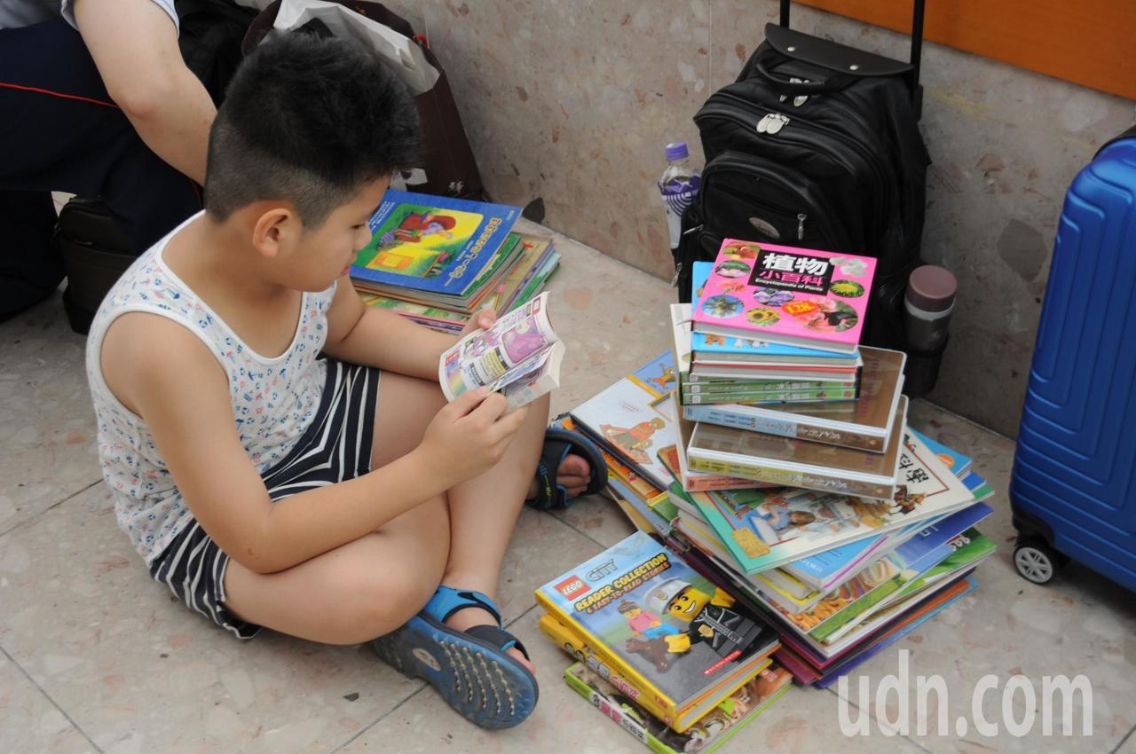 孩子翻開書本簡單閱讀,把喜歡的書籍帶回家。記者郭宣彣/攝影