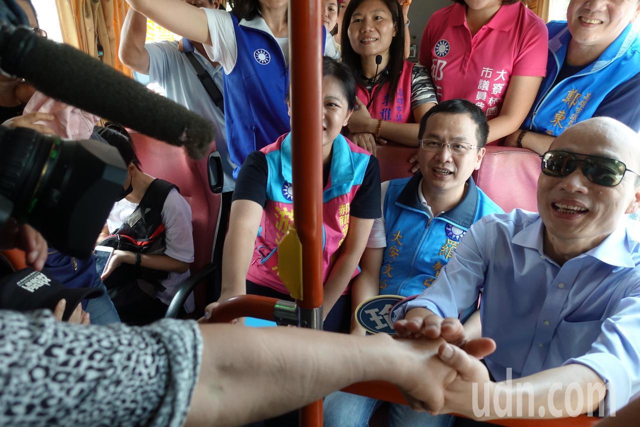 韓國瑜(右)在公車上獲悉有台北市民特別一早從台北下來聲援,相當感動,握著民眾的手...