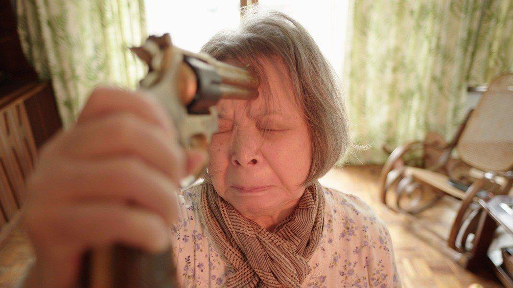 資深演員梅芳演出「水槍」,戲中舉起水槍佯裝自殺。圖/公視提供  ※ 屬戲劇效果,