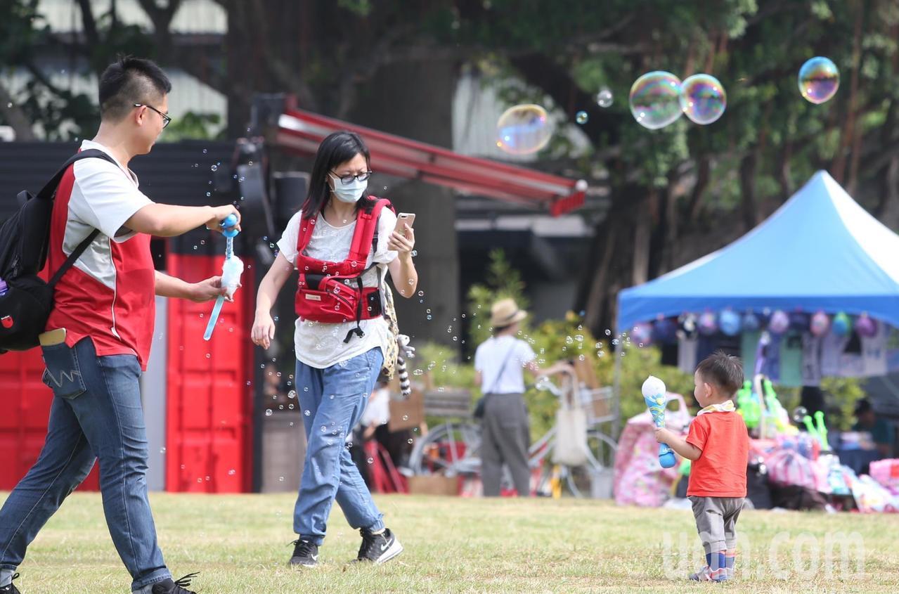 陣雨過後天氣放晴,公園裡媽媽為幼兒拍照,一旁的爸爸用泡泡製造效果。記者侯永全/攝...