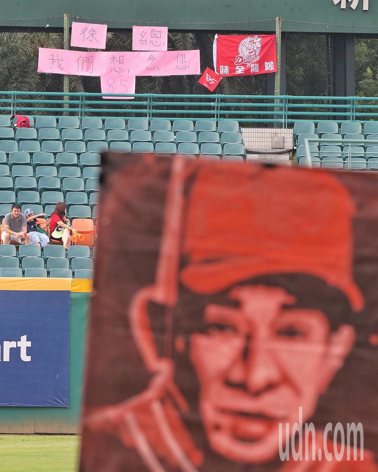 街頭表演藝術家在賽前畫出前義大犀牛總教練徐生明漆畫像,有球迷掛上味全龍隊旗並貼出...