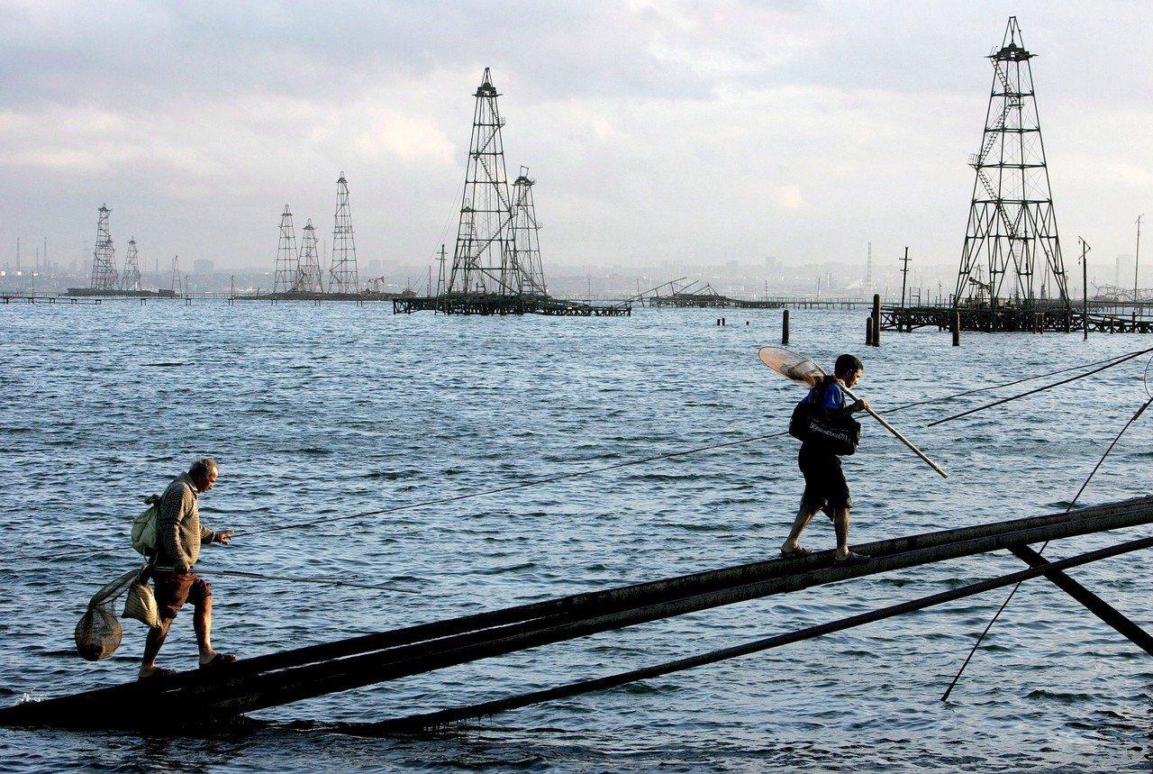 裏海的油氣儲量豐富。圖為兩名水手在靠近亞塞拜然的裏海油井井架前行走。歐新社