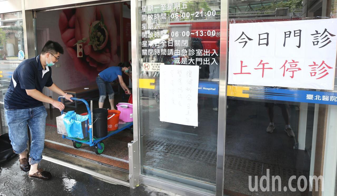 新莊台北醫院貼出上午停診公告,員工則忙於排除大廳內的積水。聯合報記者侯永全/攝影