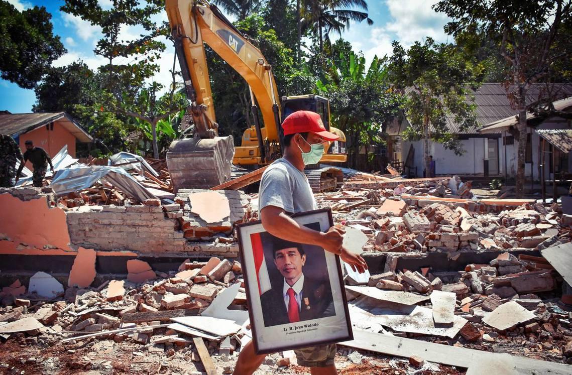 龍目島房屋倒塌嚴重,部分災區已形同廢墟。圖為災地抱著印尼總統佐科威照片的民眾。 ...