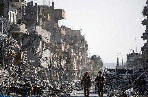 2017年10月的檔案照顯示,IS宣稱的首都拉卡已成廢墟,街上的兩名軍人隸屬於美...