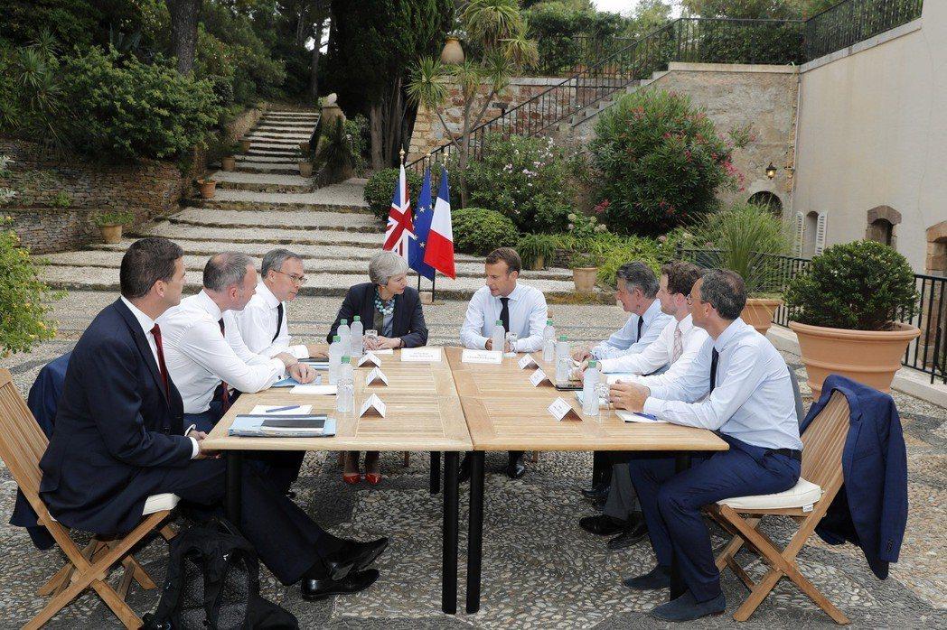 法國總統馬克宏(中右)3日在避暑官邸布雷岡松堡與英國首相梅伊(中左)會談。 (美...