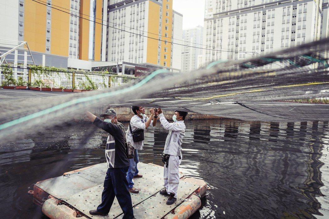 亞運在雅加達:選手村外的河川污染,利用黑網遮蓋,眼不見為淨。 圖/歐新社