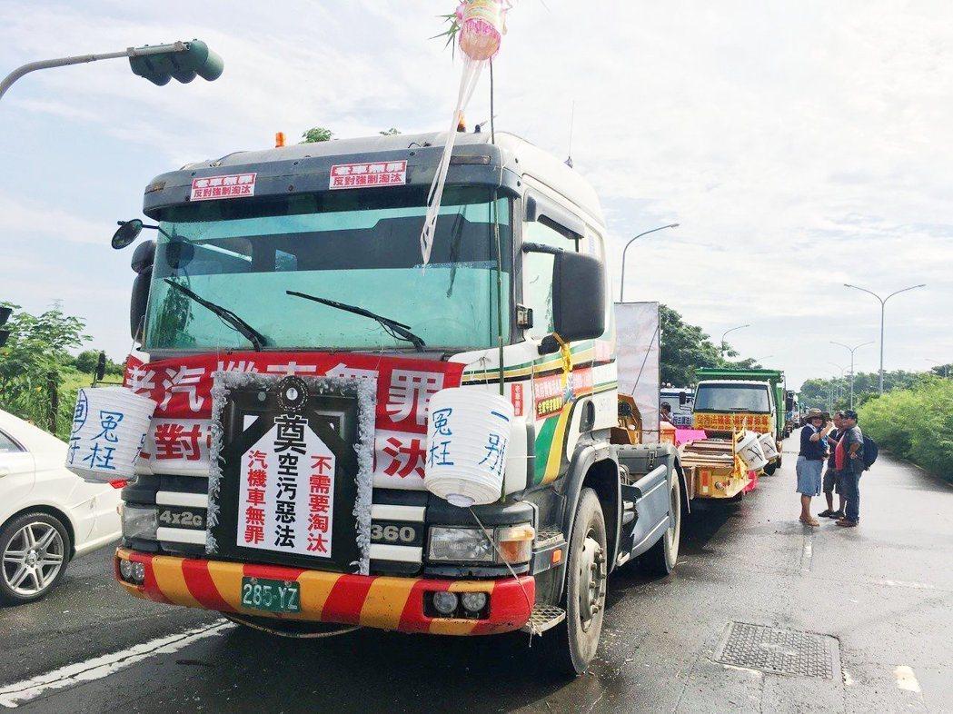 老汽機貨車自救會今天集結在高鐵台南站附近,遊行抗議空污法扼殺他們的生計。 記者吳...