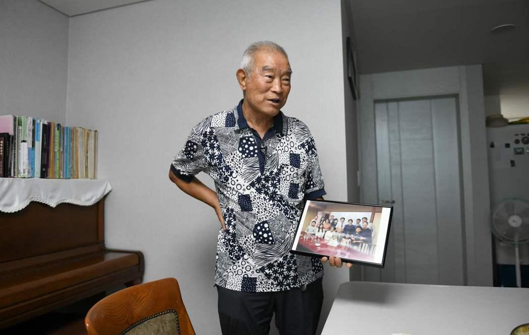 金光浩在首爾家中受訪,拿出他在南韓的全家福照片,準備要給北韓的弟弟看。 法新社