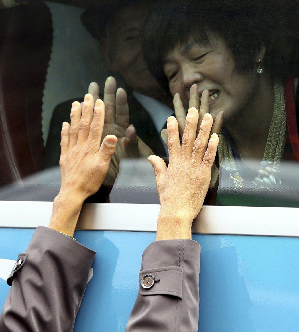 2015年兩韓離散家屬團聚結束後,一名坐在巴士上即將離去的南韓婦人伸出雙手貼著玻...