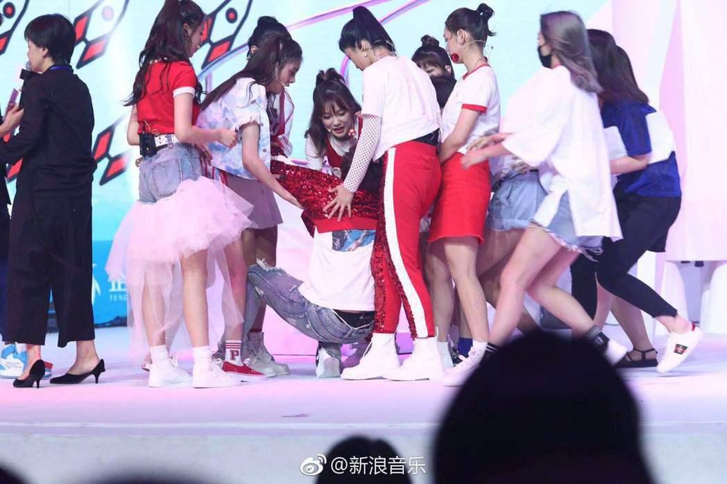 「火箭少女101」的Sunnee(中)在台上暈倒,成員急忙扶住他。圖/摘自微博