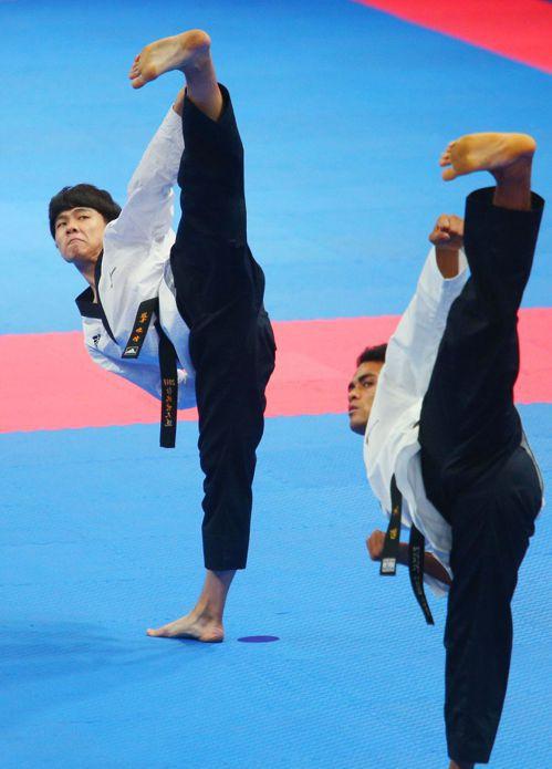 跆拳道國手陳靖(左)在亞運品勢男子個人項目首戰輕鬆擊敗尼泊爾選手,晉級8強。特派...