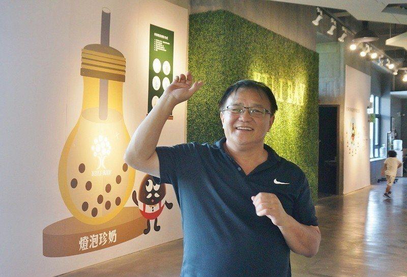 上統食品董事長陳家昇走在奇麗灣珍奶觀光工廠裡,牆上繪製的正是旅客來此必喝的人氣商...