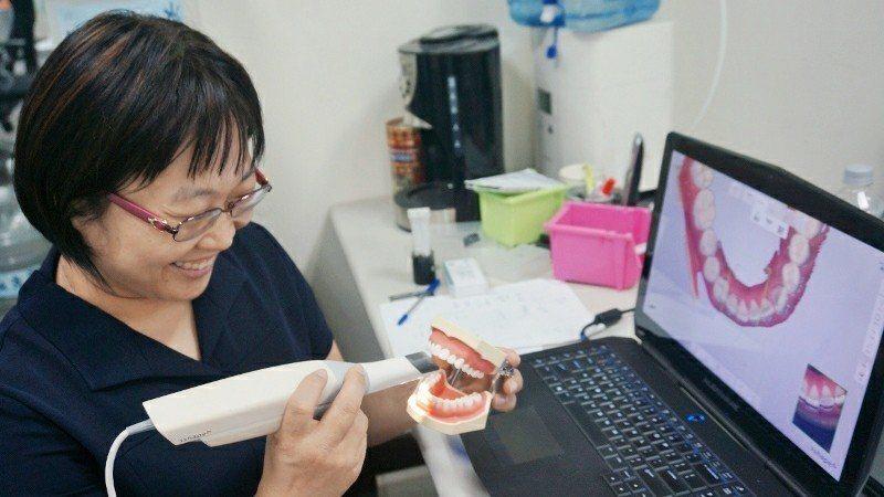家誠全球數位醫材董事長蔡幸君示範口掃機的操作。 徐谷楨/攝影
