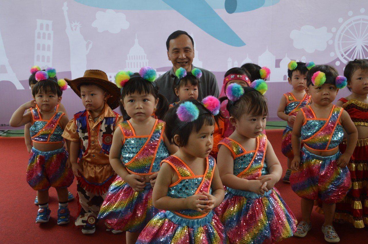 新北市長朱立倫察和裕民公托啟用典禮上表演幼童合照,和家長寒暄。記者施鴻基/攝影