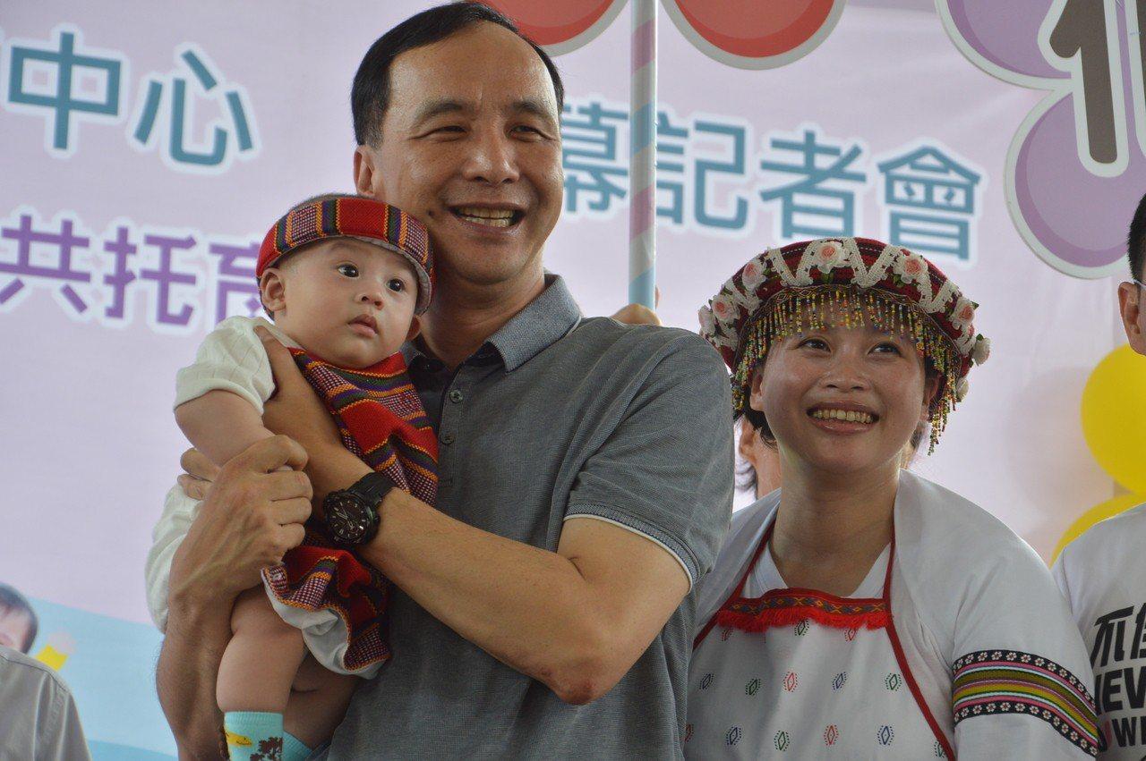 新北市長朱立倫抱起裕民公托中心保育員施淑玲5個月大的孩子,宣布公托啟用。記者施鴻...