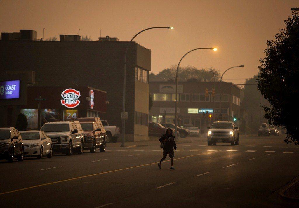 加拿大西部的林火蔓延讓鄰近城市籠罩在一片煙霧中,圖為上午10點多時,一名路人在黑...