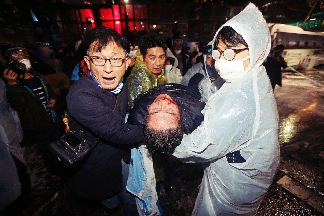 白老先生(中)後腦遭水柱擊中,被其他示威民眾從地上拉起時,呈現口鼻流血與昏迷狀態...
