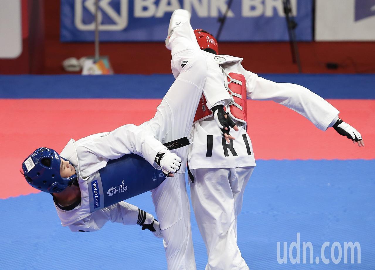 我國跆拳道選手黃鈺仁(藍色)今天在雅加達亞運男子68公斤級8強賽不敵伊朗選手,無...