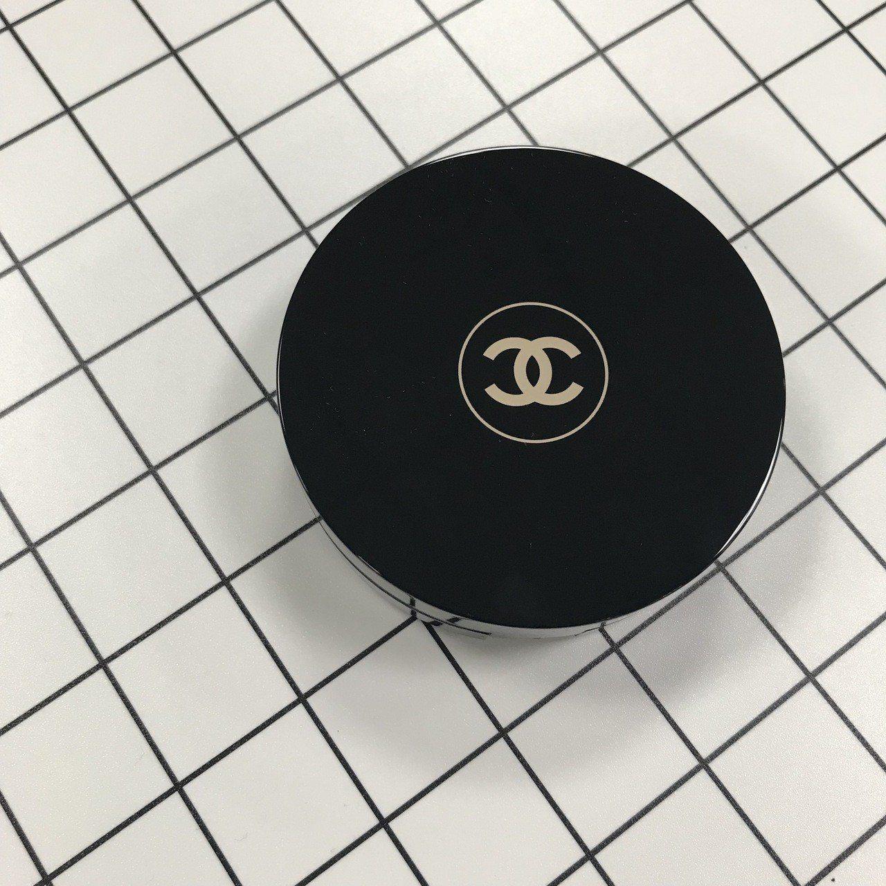 香奈兒活力光采保濕氣墊粉餅SPF15,黑色圓形外盒有著經典的雙C Logo。記者...