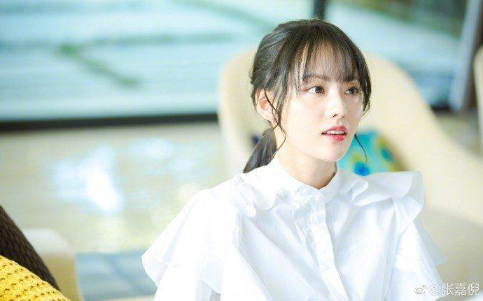 張嘉倪示範了以褶襉白襯衫搭配瀏海穿出清新學生風的訣竅。圖/取自微博