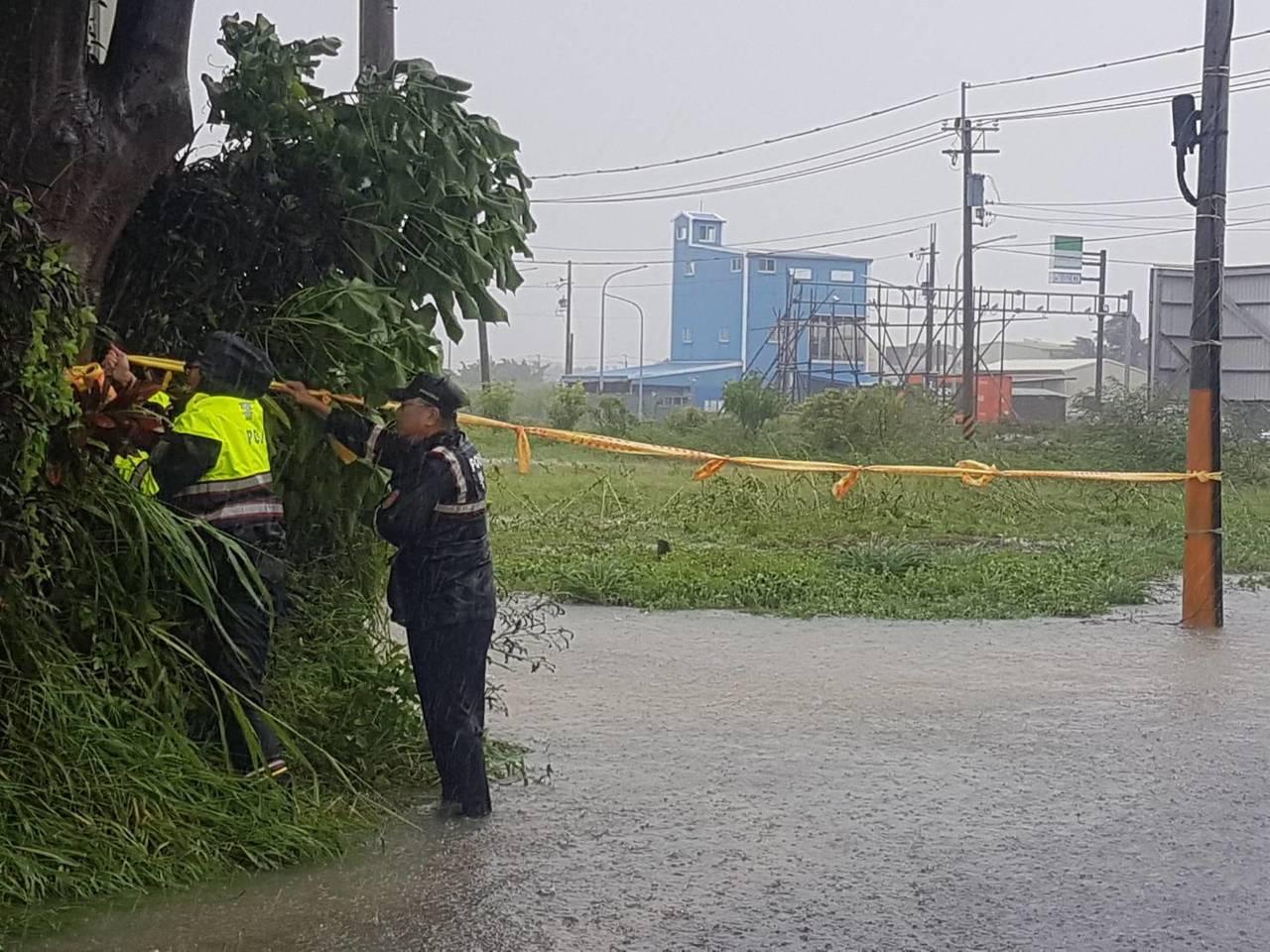 三分局員警冒著風雨封鎖路口防止人車進入受困。圖/員警提供