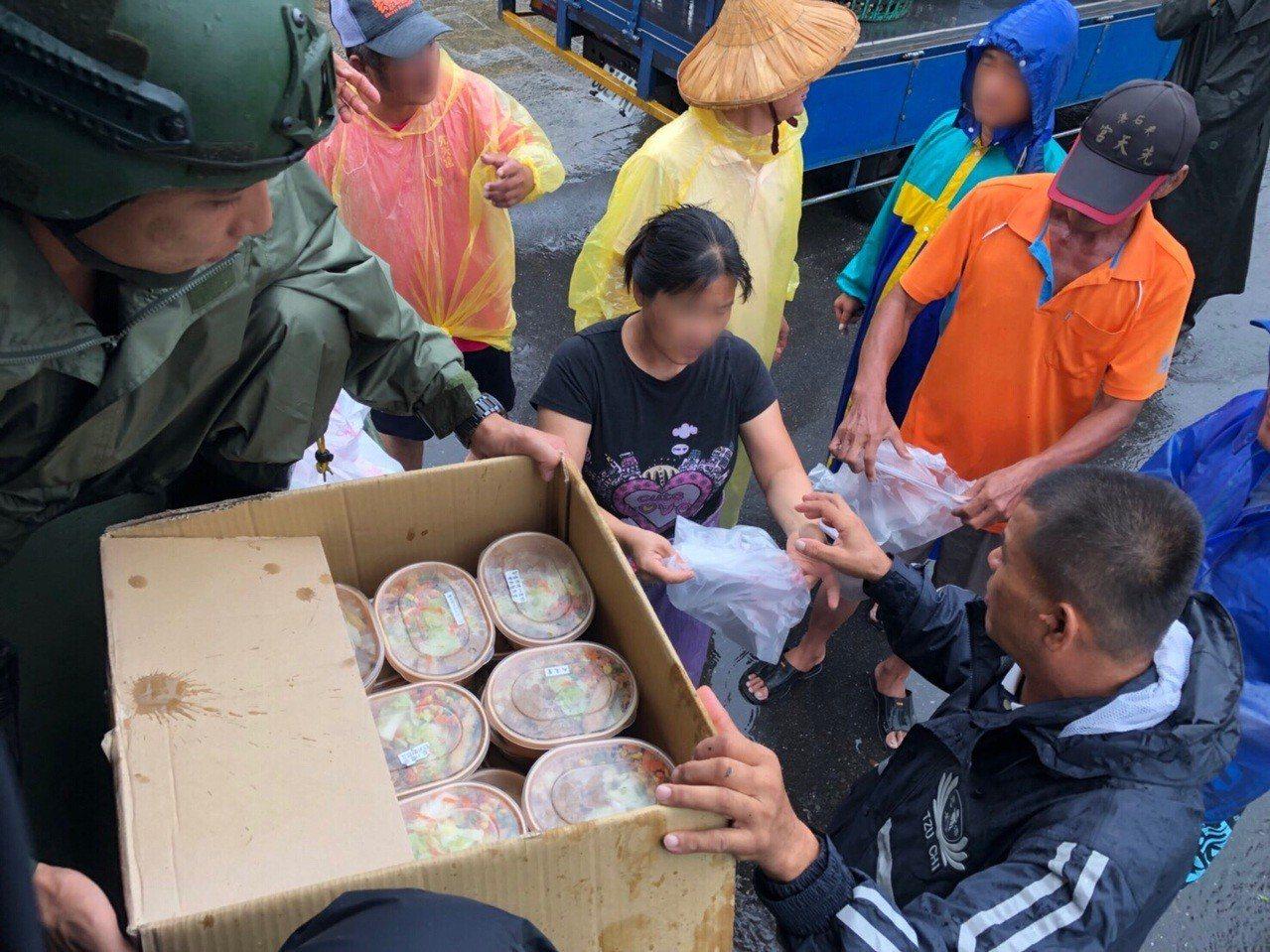 慈濟志工也在軍方協助下,涉水將熱騰騰的便當送鄉親手中。圖/慈濟基金會提供