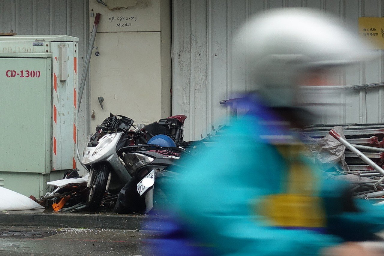 鷹架倒塌工地現場,機車殘骸移置在路旁。記者劉星君/攝影