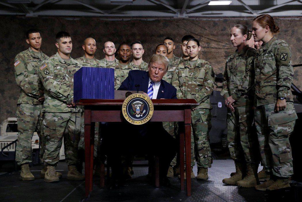 川普(中)13日在紐約州德拉姆堡陸軍基地簽署國防授權法。(路透)