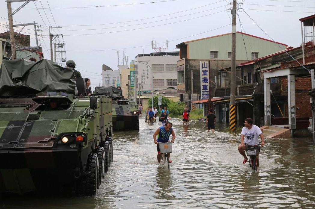 蔡英文總統搭雲豹車行過淹水街道,村民涉水或騎單車進出村落。記者謝恩得/翻攝
