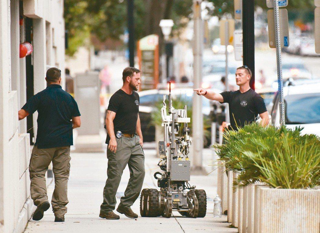 美國佛州傑克森維爾市的電玩大賽會場26日發生槍案,拆彈小組用機器人檢查垃圾桶。 ...