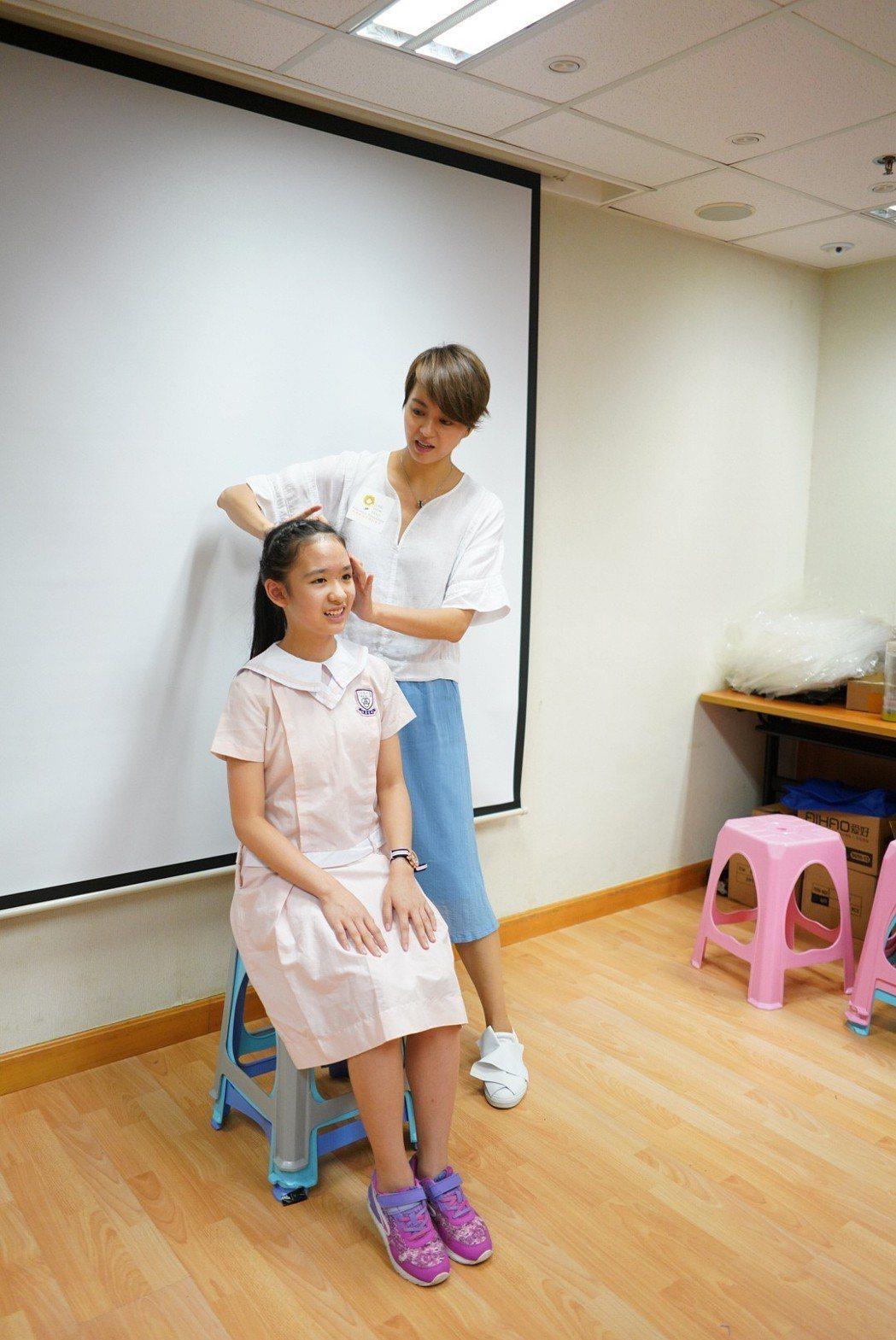 梁詠琪幫基層家庭成長的小朋友剪頭髮。圖/小黃花慈善教育基金提供