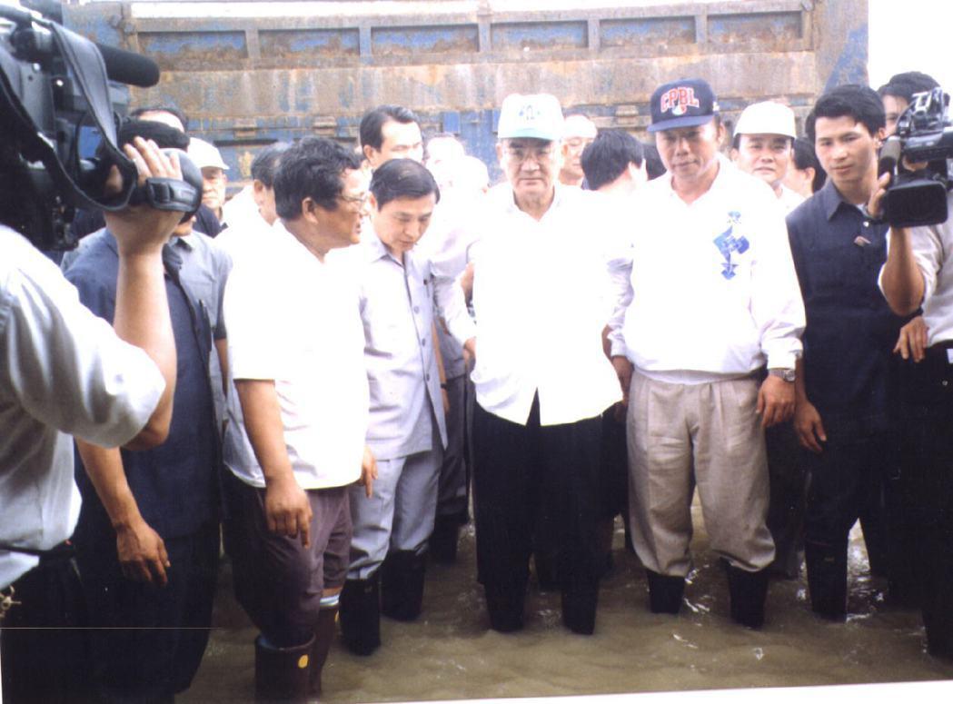 1996年連戰(中)涉水視察東石鄉災情,照片可見他雙腳泡在泥水中。 圖/聯合報系...