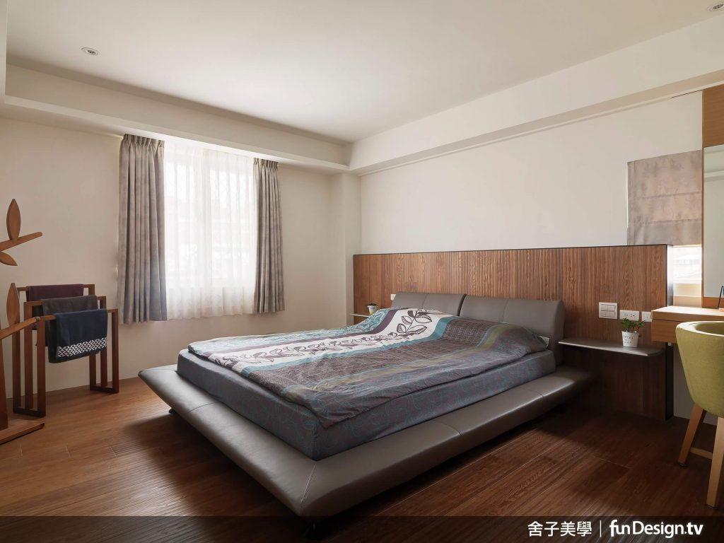 主臥房捨棄耐磨木地板,設計師改以特殊的手刮木作鋪覆地板,溫潤質理的木材延伸至床頭...