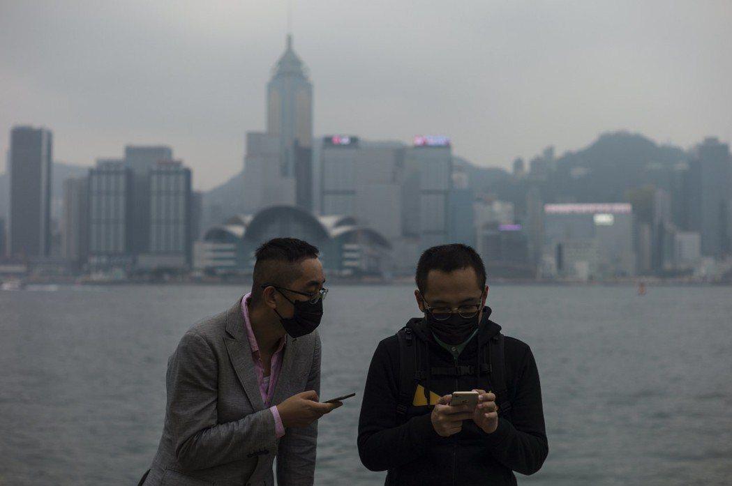 香港維多利亞港兩名男子戴口罩防空汙。歐新社